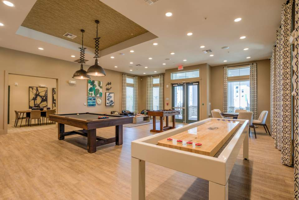Game room featuring shuffleboard, poker table, billiards and foosball